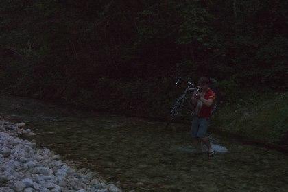 Hugo carrying his bike to riverside spot