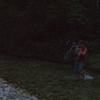 Hugo carrying his bike to riverside spot