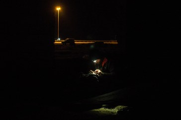 Hugo stitching his pants by torchlight. That car in the background is a police car. Two police came over to see what was going on. When they figured we were foreign they left without saying anything.
