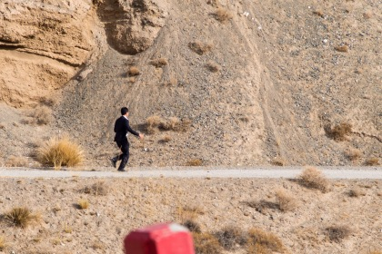 A Chinese businessman chasing an ibex for a photo